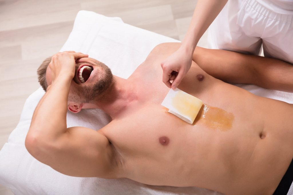 Elevated View Of Young Man Screaming While Waxing Chest In Spa
